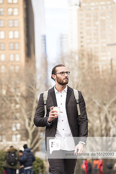 Portrait of bearded young businessman with backpack and coffee to go  New York City  USA
