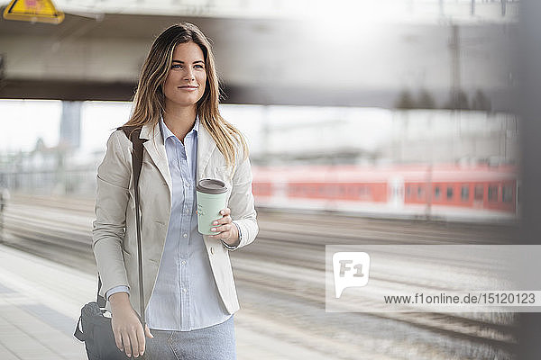 Young businesswoman with coffee to go cup  standing on station