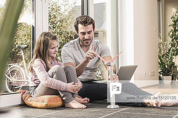 Young man and little girl playing with model of a wind turbine