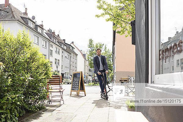 Geschäftsmann mit E-Scooter auf Bürgersteig in der Stadt
