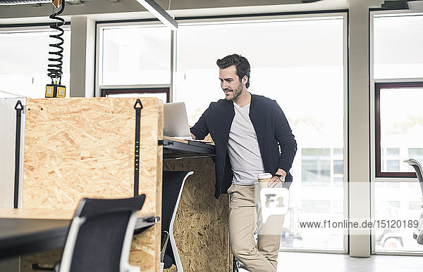 Young businessman in modern office  using laptop on high desk