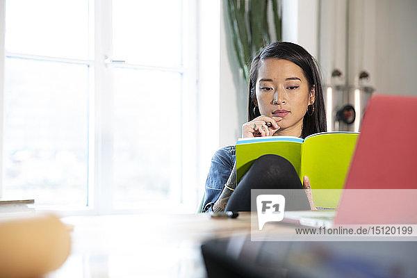 Frau  die im Büro am Tisch arbeitet und ein Buch liest