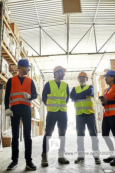 Lächelnde Arbeiter stehen in der Fabrikhalle und reden