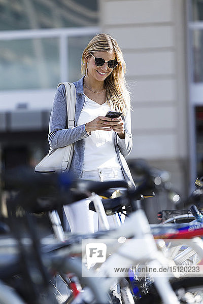 Junge Geschäftsfrau schreibt beim Gehen mit ihrem Handy SMS