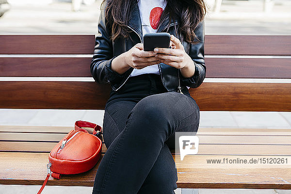 Young woman sitting on a bench  using smartphone
