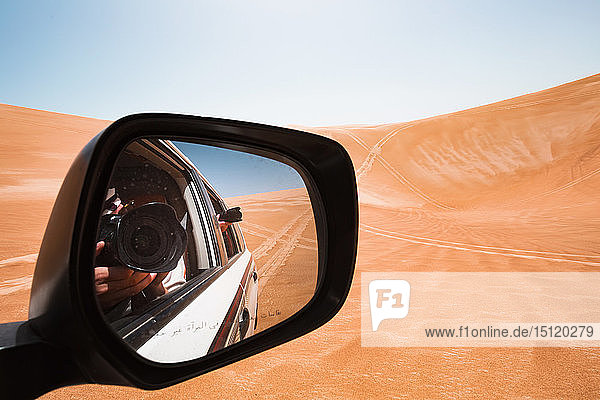 Mirror image of a man taking pictures from a off-road vehicle,  Oman,  Wahiba Sands