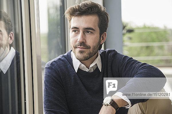 Porträt eines jungen Geschäftsmannes  der am Fenster sitzt
