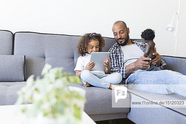 Vater und Tochter sitzen zu Hause auf dem Sofa mit Puppe und Tablette