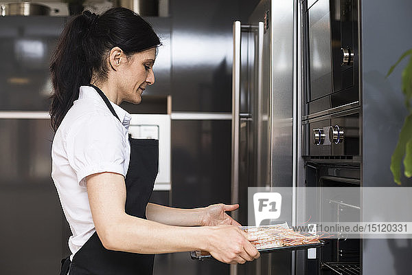 Woman putting baking tray with shrimps into oven