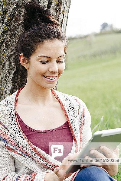 Lächelnde junge Frau sitzt mit Tablette an einem Baum auf dem Land
