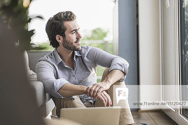 Young man sitting at home on floor  using laptop  looking out of window