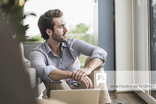 Junger Mann sitzt zu Hause auf dem Boden  benutzt einen Laptop und schaut aus dem Fenster
