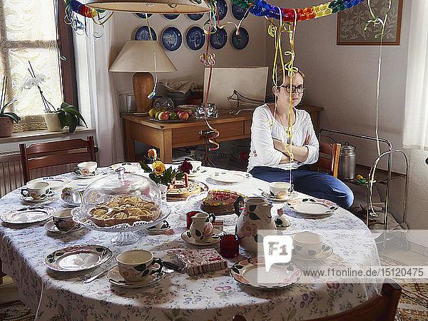 Frau in schlechter Stimmung wartet am gedeckten Tisch auf Gäste