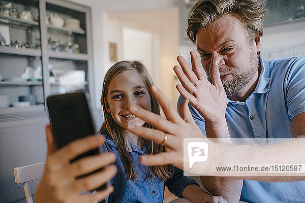 Playful father and daughter taking a selfie at home