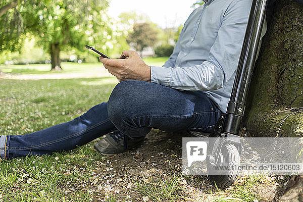 Mann sitzt auf einem E-Scooter in einem Park und lehnt sich an einen Baumstamm  während er ein Smartphone benutzt  Teilansicht