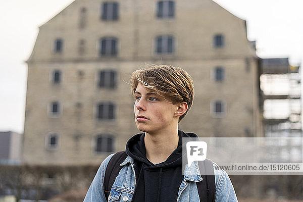 Dänemark  Kopenhagen  junger Mann vor einem Gebäude  der sich umsieht