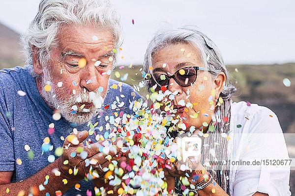 Älteres Ehepaar bläst Konfetti im Freien