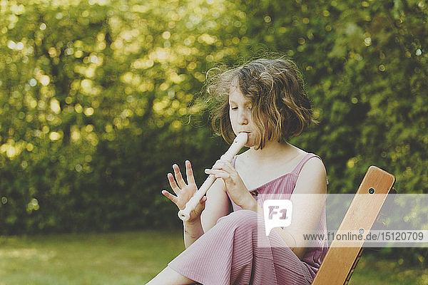 Ein Flöte spielendes Mädchen im Garten