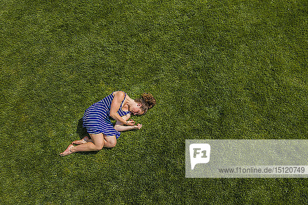 Aerial view of a young woman lying on a meadow