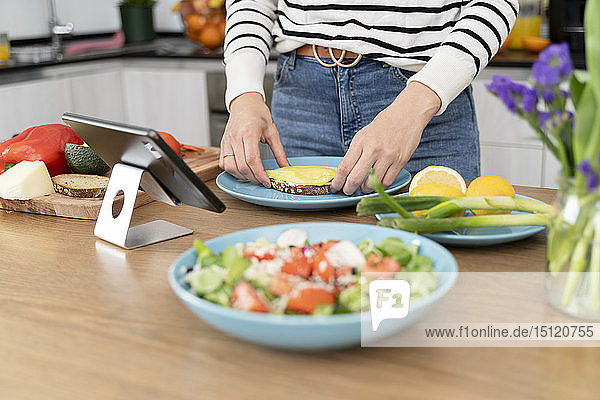Frau steht in der Küche und bereitet Salat für das Mittagessen