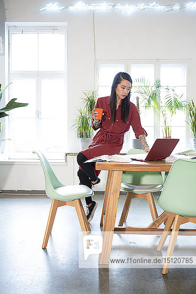 Woman using laptop on table in office