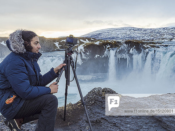 Iceland  photographer at Godafoss Waterfall in winter