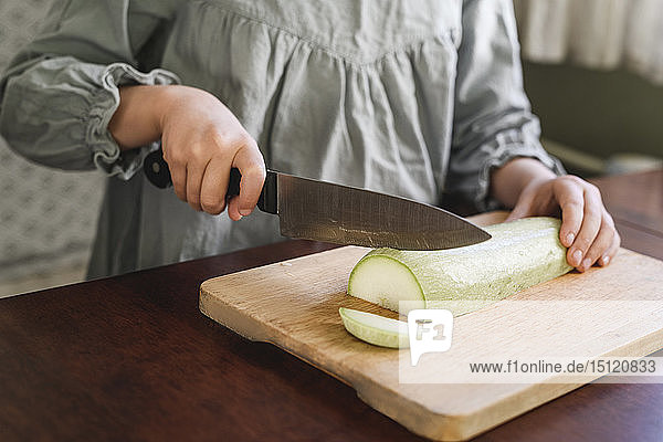 Girl's hands slicing courgette,  partial view