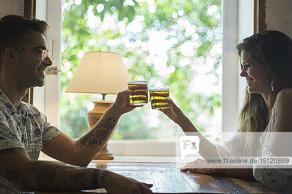 Glückliches junges Paar  das am Tisch eines Restaurants mit Biergläsern klimpert