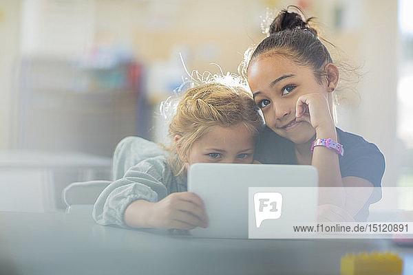 Porträt von zwei lächelnden Mädchen  die sich im Kindergarten eine Mini-Tablette teilen