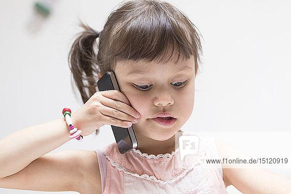 Porträt eines kleinen Mädchens am Telefon mit Blick nach unten