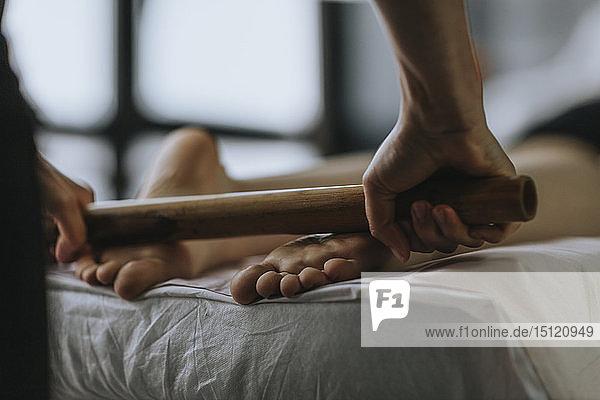 Nahaufnahme einer Massagetherapeutin mit einer Rolle auf den Fußsohlen einer Frau