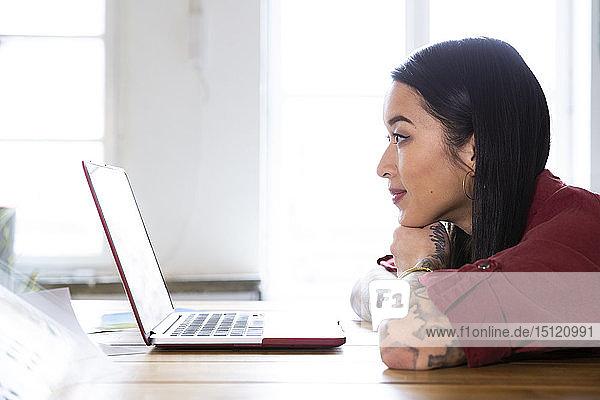Frau benutzt Laptop am Tisch im Büro