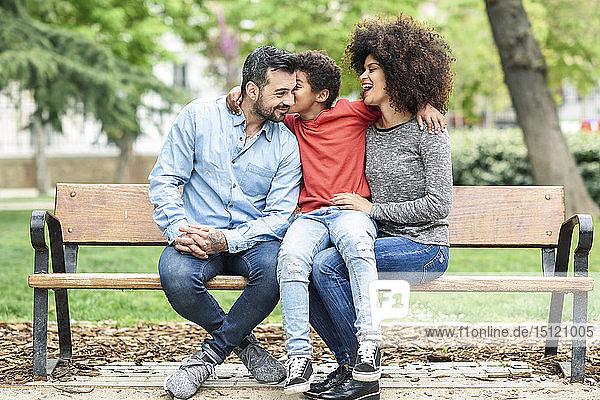 Familie sitzt auf einer Parkbank  Sohn küsst Vater