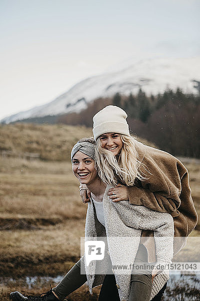 UK  Scotland  happy young woman carrying friend piggyback in rural landscape