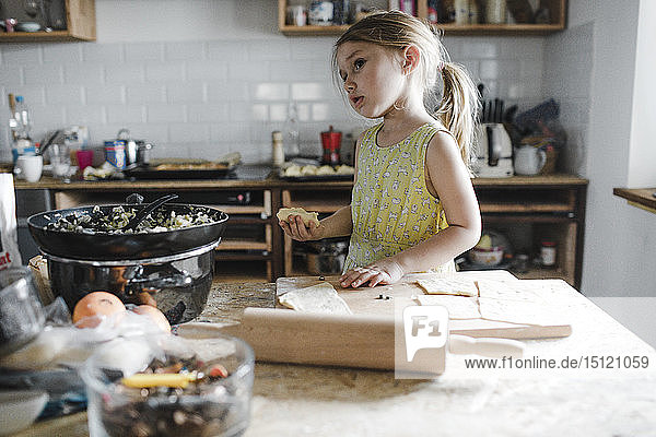 Little girl preparing stuffed pastry in the kitchen