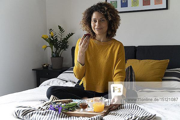 Frau sitzt im Bett und frühstückt gesund