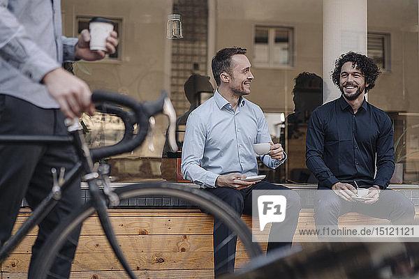 Freunde sitzen vor dem Kaffeehaus  unterhalten sich  trinken Kaffee