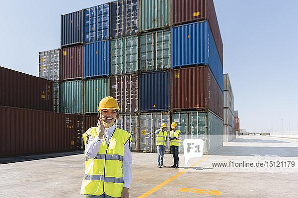 Arbeitnehmerin am Telefon vor Kollegen und Frachtcontainern auf einem Industriegelände