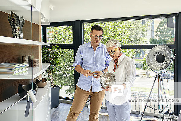 Man and mature woman looking at glass bowl in a furniture retail store