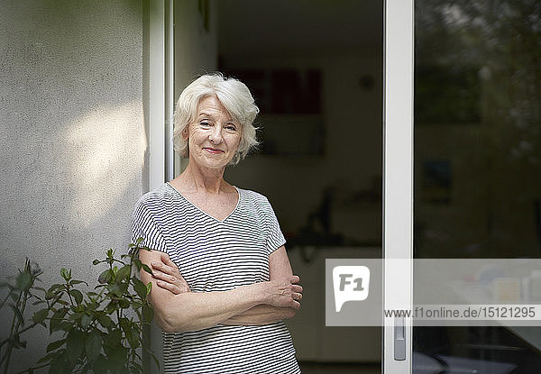 Portrait of smiling mature woman standing in front of open terrace door in the evening
