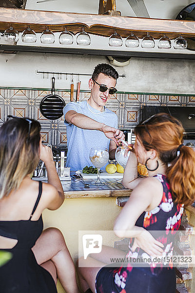 Barkeeper preparing drinks for two women at a bar