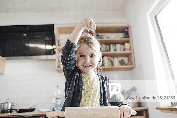 Portrait of smilingl ittle girl rolling out dough in the kitchen