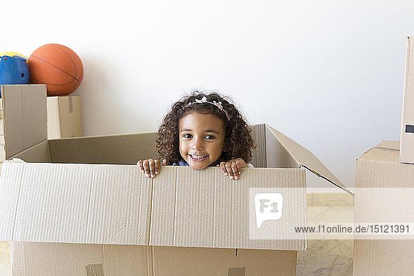 Porträt eines glücklichen Mädchens  das aus einem Pappkarton in sein neues Zuhause schaut