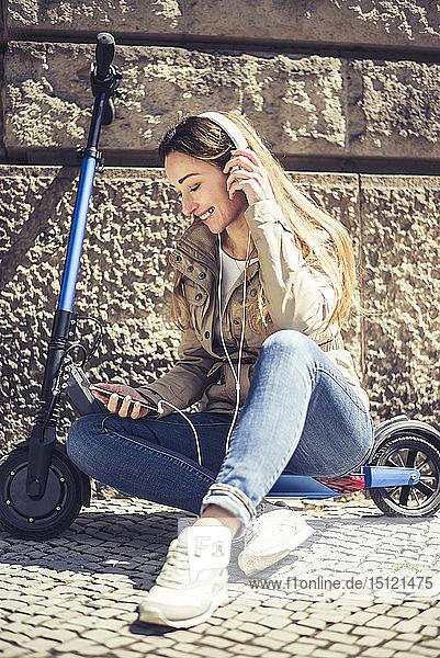 Glückliche Frau sitzt auf einem E-Scooter und hört Musik mit Kopfhörern und Smartphone