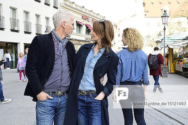 Ein erwachsenes Paar geht in der Stadt spazieren,  der Mann kümmert sich um eine andere Frau