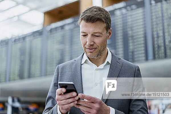 Porträt eines Geschäftsmannes  der auf dem Flughafen ein Mobiltelefon benutzt
