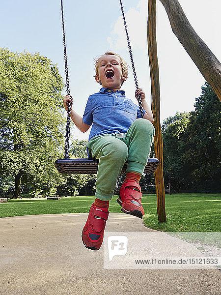 Porträt eines schreienden kleinen Jungen auf der Schaukel