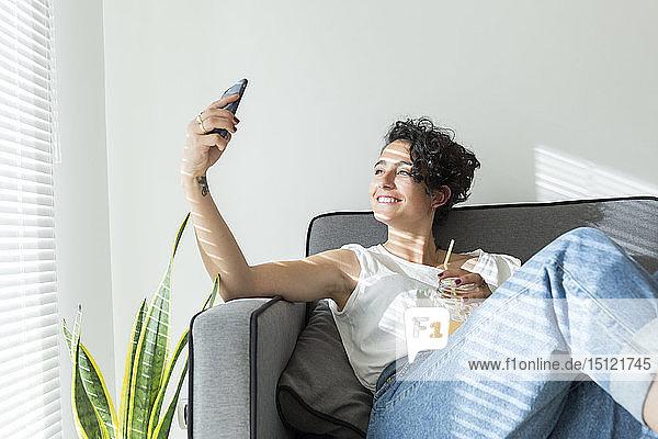Lächelnde junge Frau  die mit einem Erfrischungsgetränk auf der Couch sitzt und ein Selfie nimmt