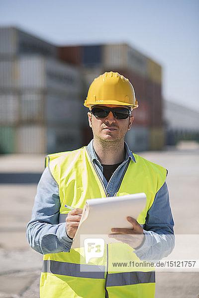 Porträt eines Arbeiters mit einem Notizblock in der Nähe von Frachtcontainern auf einem Industriegelände