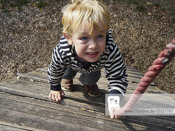 Porträt eines kleinen Jungen auf Klettergerüst